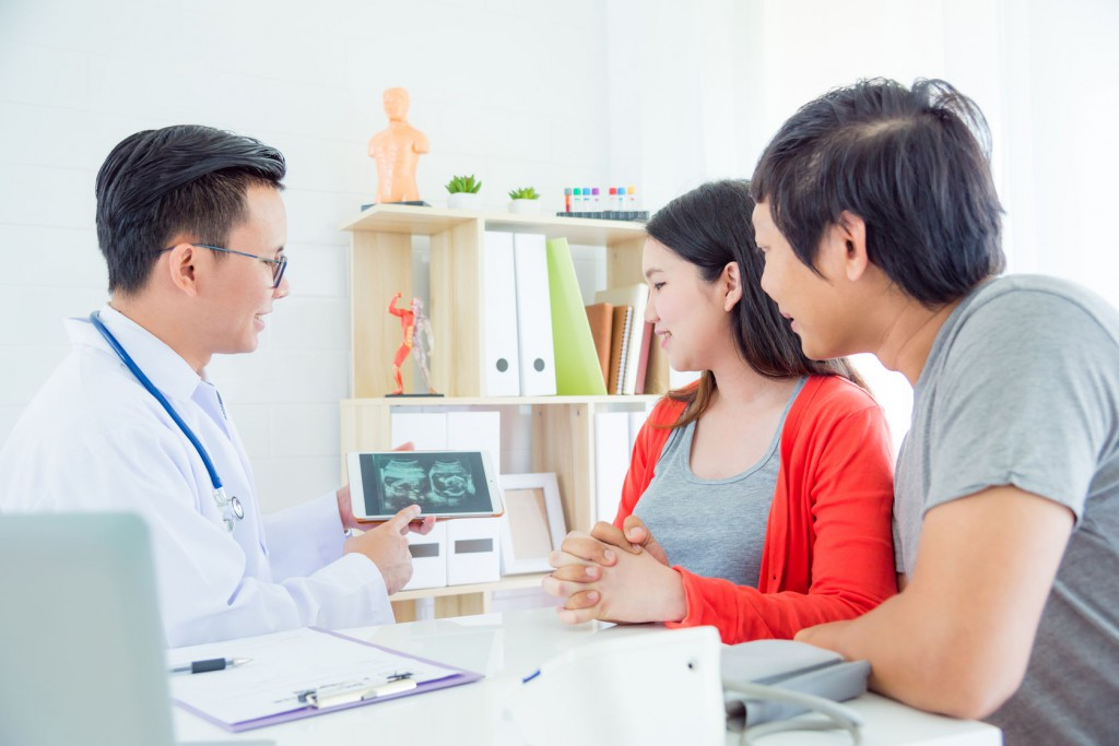 Asian Doctor explain ultrasound result to asian couple at hospit